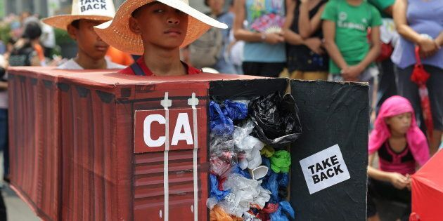 Filipino environmental activists protest outside the Canadian embassy at the financial district of Makati,...