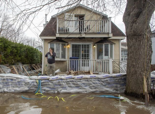 Marc-Andre Forget keeps an eye on the floodwaters in front of his home April 25, 2019 in Laval,