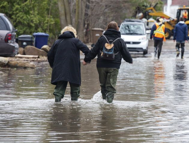 Residents wade through a flooded street on April 25, 2019 in Laval,