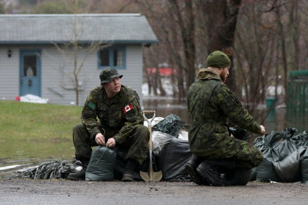 Members of the Canadian Forces prepare sandbags in the flooded Constance Bay area in