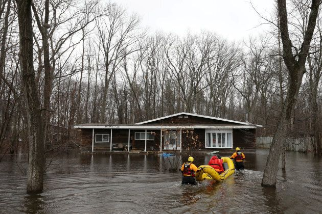 Officials walk in the water to check on a flooded home in the Constance Bay area in