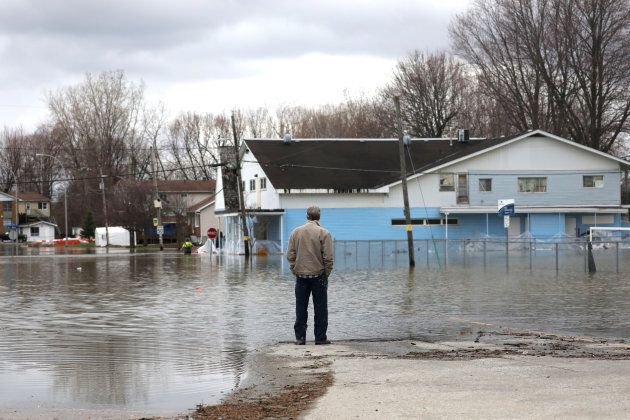 A man looks out at a flooded residential area in Gatineau,