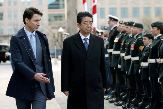 Canada's Prime Minister Justin Trudeau and Japan's Prime Minister Shinzo Abe inspect the honour guard...
