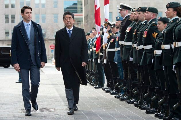 Prime Minister Justin Trudeau walks with Japanese Prime Minister Shinzo Abe as he inspects an honour...