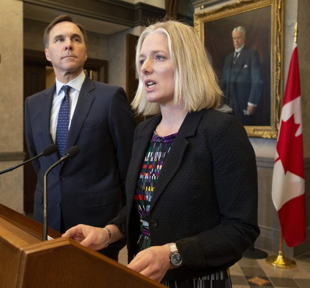 Finance Minister Bill Morneau looks on as Environment Minister Catherine McKenna speaks in the foyer of the House of Commons in Ottawa on April 29, 2019.