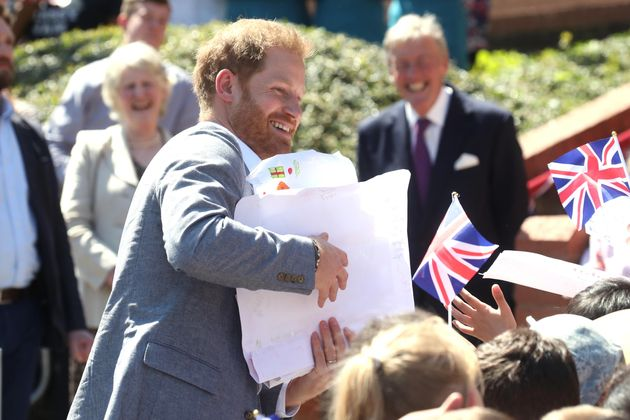 The Duke of Sussex receives gifts from well-wishers as he arrives for a visit to the Barton Neighbourhood