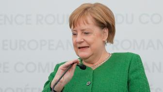German Chancellor Angela Merkel adjusts her microphone during a press conference at the end of an EU summit in Sibiu, Romania, Thursday, May 9, 2019. European Union leaders on Thursday start to set out a course for increased political cooperation in the wake of the impending departure of the United Kingdom from the bloc.(AP Photo/Vadim Ghirda)