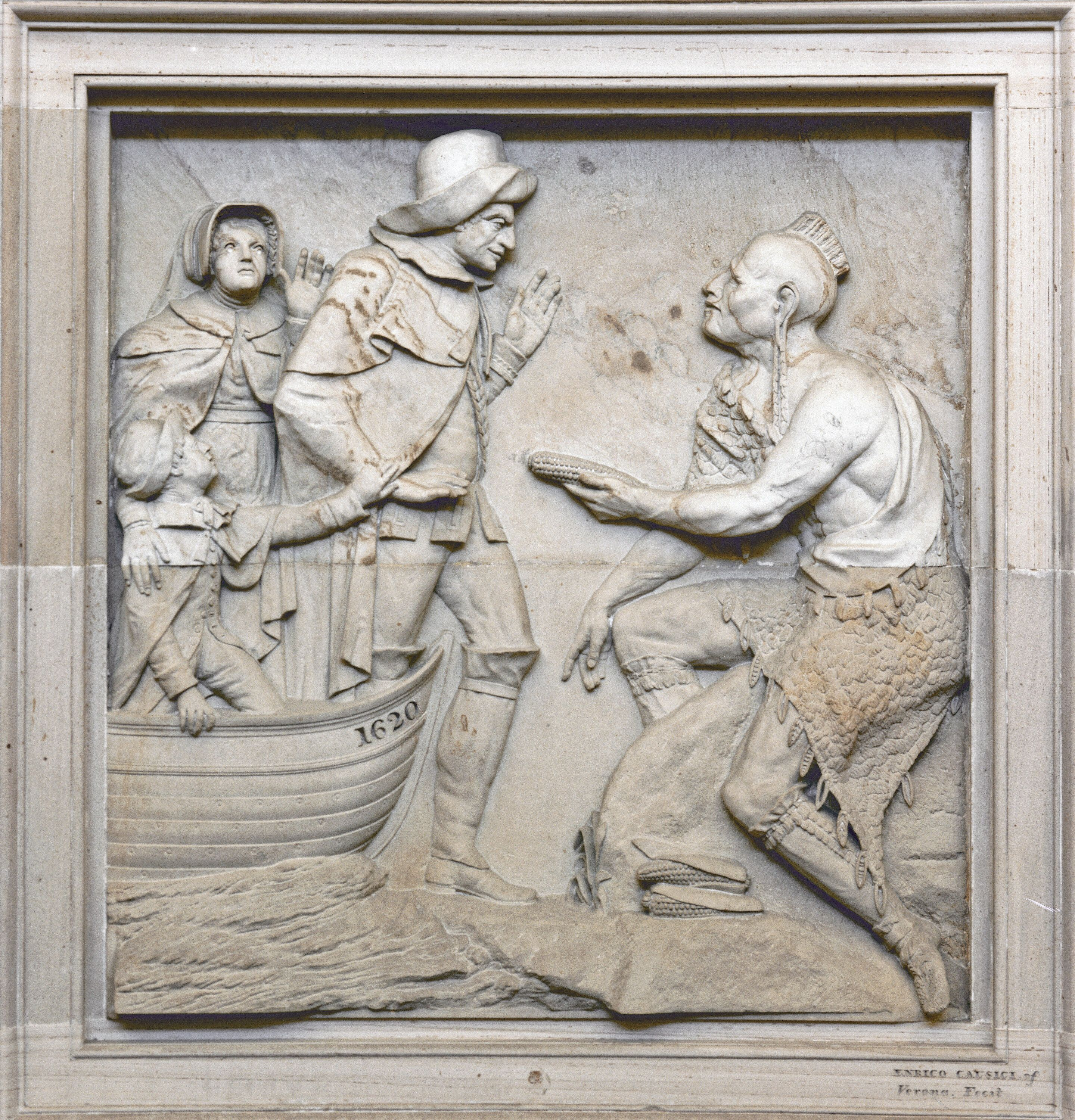 A hunched Indian offers corn to a settler stepping out of a boat labeled 1620. Sandstone carving by Enrico Causici, 1825.