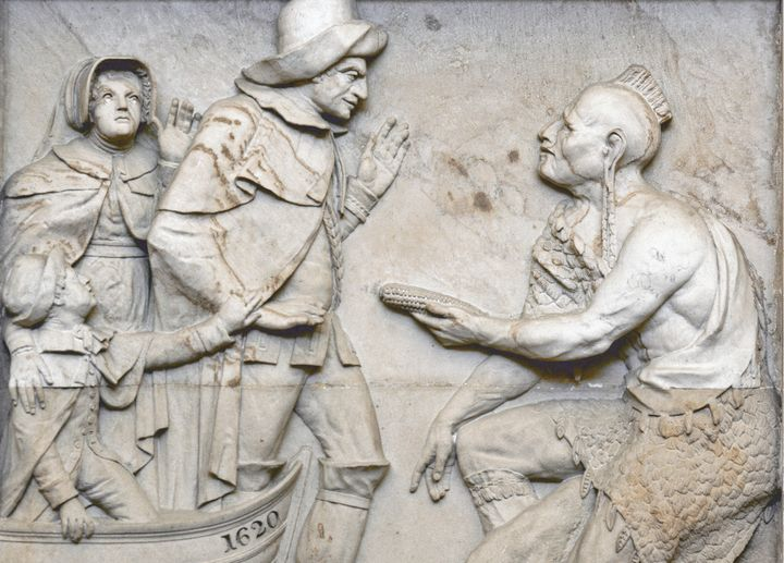 """Landing of the Pilgrims,"" an 1825 sandstone carving in the Capitol Rotunda, shows a Native man bowing down to a colonizer wi"