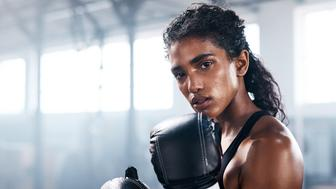 Cropped portrait of an attractive and athletic young female boxer working out in the gym