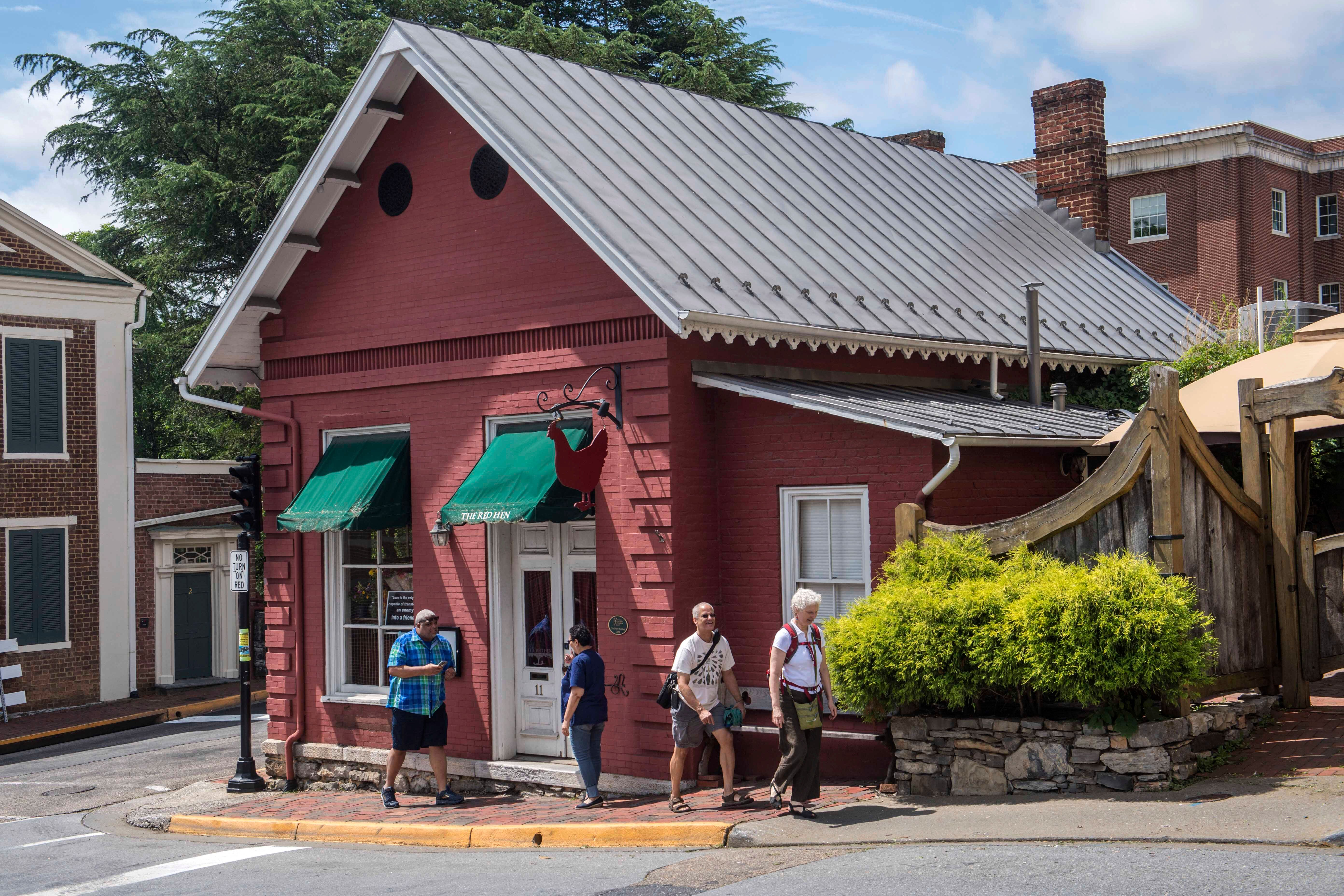 People walk past the Red Hen restaurant in Lexington, Va., Wednesday, June 27, 2018. The co-owner of the Virginia restaurant that refused to serve White House press secretary Sarah Huckabee Sanders has resigned from a local business group. (AP Photo/Don Petersen)