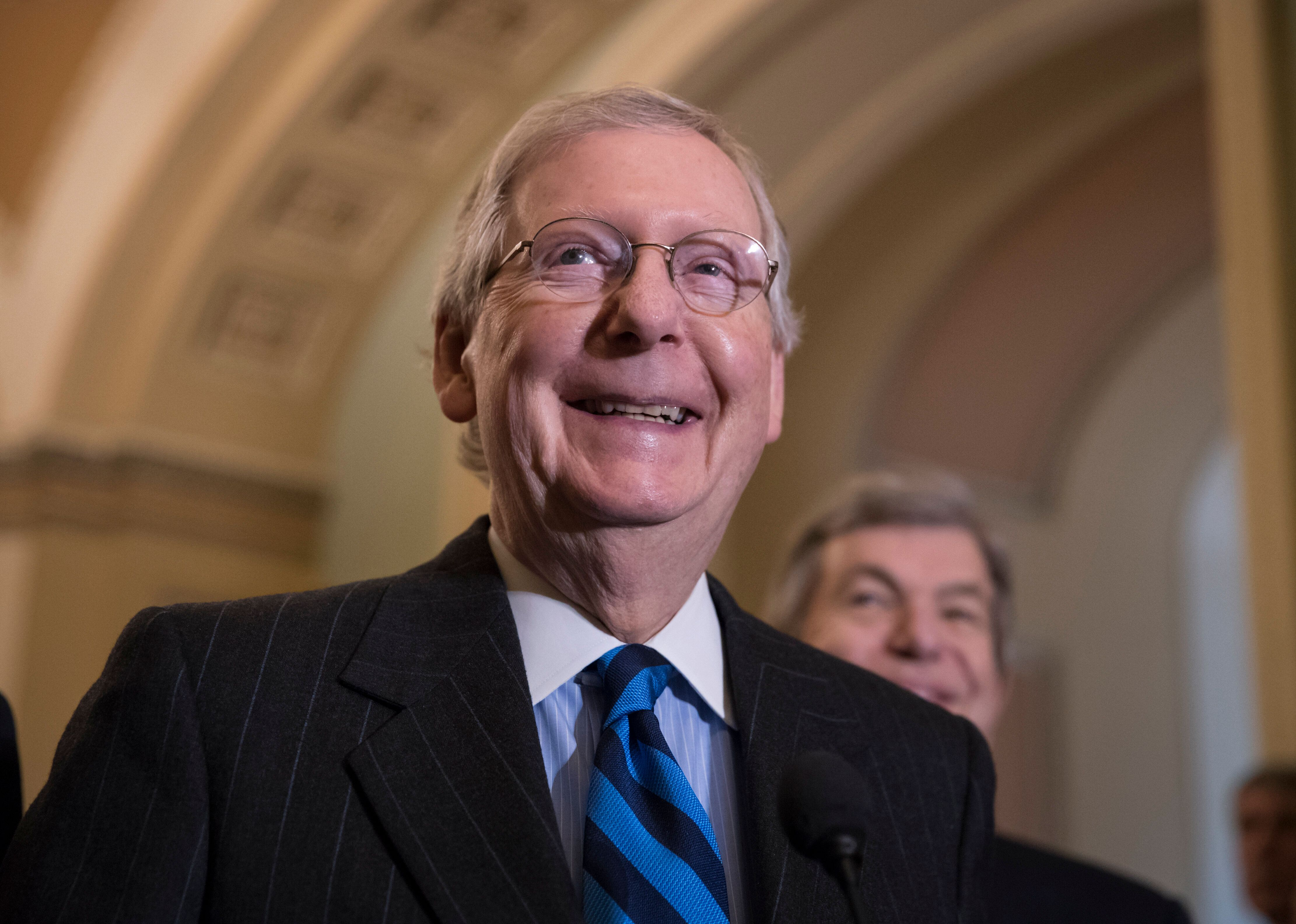 Senate Majority Leader Mitch McConnell, R-Ky., smiles as he meets with reporters as work continues on a plan to keep the government as a funding deadline approaches, at the Capitol in Washington, Tuesday, Feb. 6, 2018. (AP Photo/J. Scott Applewhite)