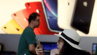 A customer looks at her iPhone in a store of U.S. tech company Apple in Beijing on Friday, May 10, 2019. U.S. President Donald Trump's latest tariff hike on Chinese goods took effect Friday and Beijing said it would retaliate, escalating a battle over China's technology ambitions and other trade tensions. (AP Photo/Ng Han Guan)
