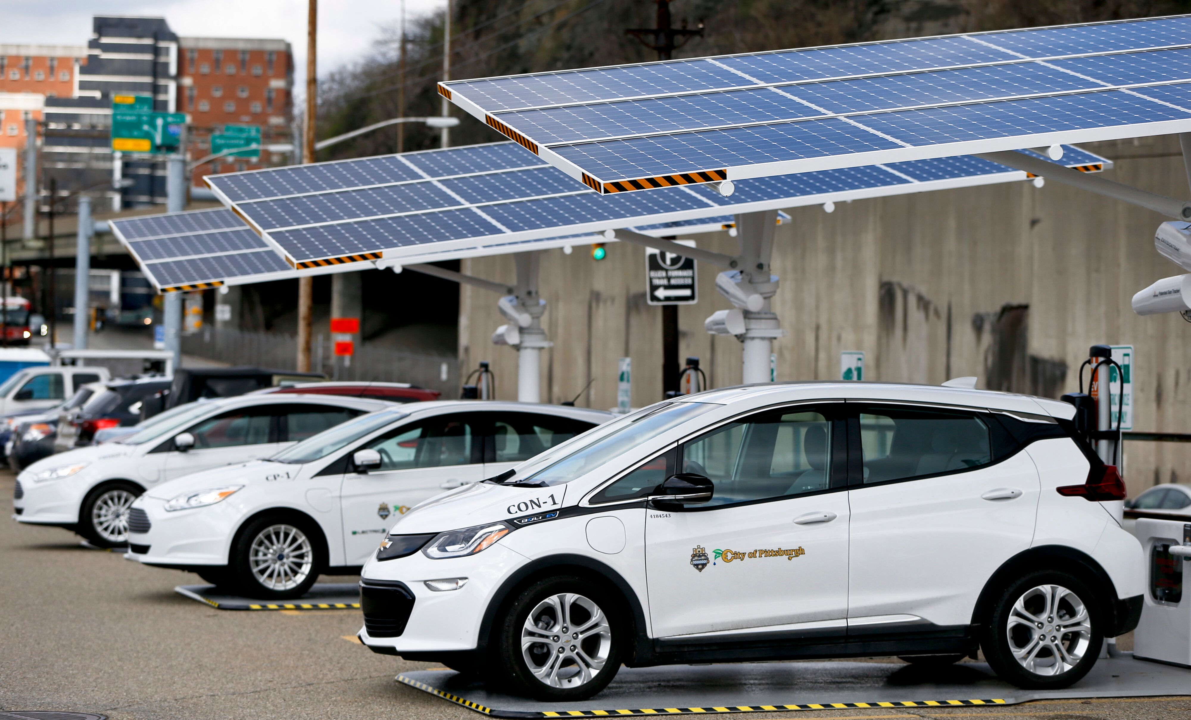 Some of the city of Pittsburgh's fleet of electrical vehicles are parked under solar charging panels before a news conference announcing the facility debut, Wednesday, April 18, 2018, in Pittsburgh. The press release from the city says that they currently have four electric vehicles and later this year they will receive six more cars that will be charged at these stations. According to the city, half of the $84,000 cost of each unit will be reimbursed through the State's Alternative Fuels Incentive Grant (AFIG). (AP Photo/Keith Srakocic)