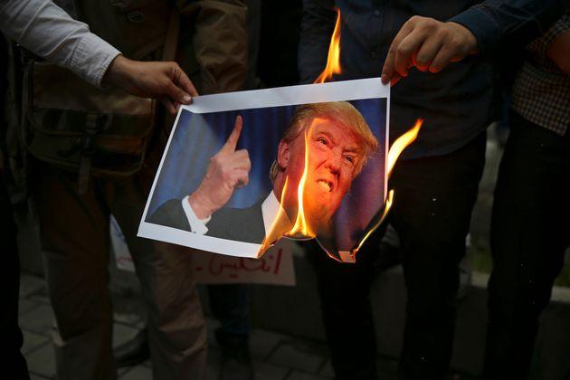 미국의 이란 핵협정 탈퇴 결정에 반발한 이란 시위대가 옛 미국 대사관 앞에서 도널드 트럼프 대통령의 사진을 불태우고 있다. 이란, 테헤란. 2018년
