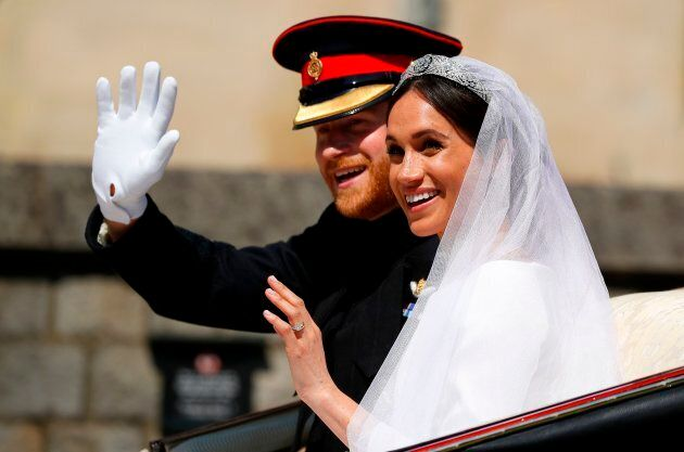 Britain's Prince Harry, Duke of Sussex and his wife Meghan, Duchess of Sussex wave from the Ascot Landau Carriage during their carriage procession on Castle Hill outside Windsor Castle in Windsor, on May 19, 2018 after their wedding ceremony.