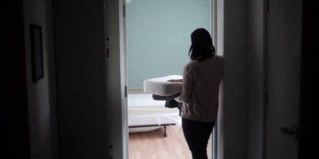 A staff member carries bedding in one of the suites at Toronto's Interval House, an emergency shelter for women in abusive situations, on Feb. 6, 2017.