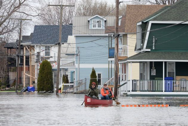 Two men paddle along Jacques-Cartier Street, past sandbagged and flooded homes in Gatineau on May 2,
