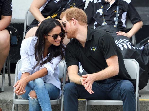 Meghan Markle and Prince Harry, probably whispering