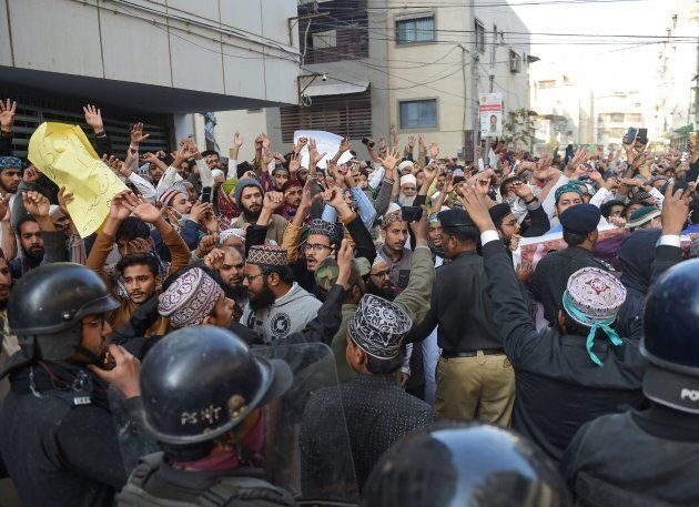 Pakistani policemen stop Islamist activists during a protest against the Supreme Court decision on the...