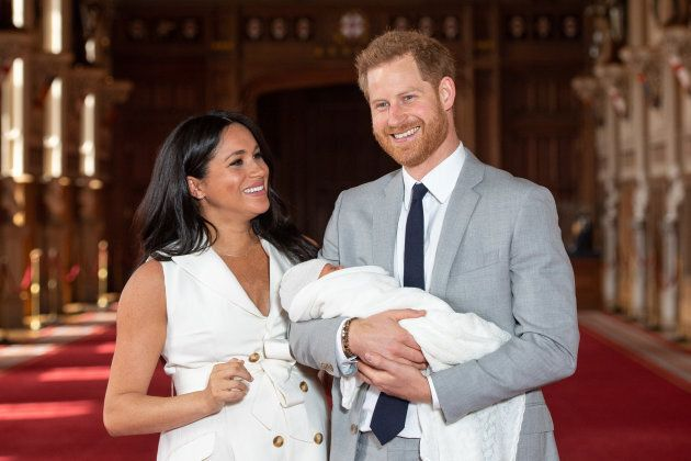 Prince Harry, Duke of Sussex and Meghan, Duchess of Sussex, pose with their newborn son during a photocall in St George's Hall at Windsor Castle on May 8, 2019 in Windsor, England. Meghan is probably trying not to laugh too hard, because of, you know, the white.