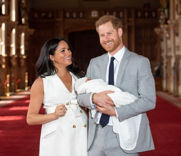 Prince Harry, Duke of Sussex and Meghan, Duchess of Sussex, pose with their newborn son Prince Archie Harrison Mountbatten-Windsor in St George's Hall at Windsor Castle on May 8, 2019 in Windsor, England.