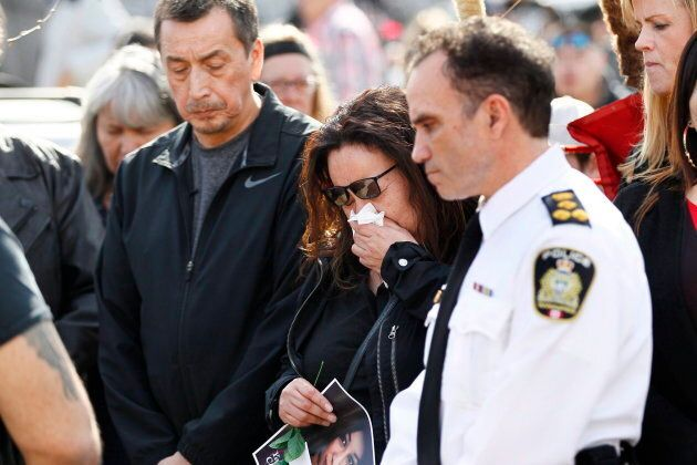 Melinda Wood weeps as she attends a walk for her daughter Christine with her husband George Wood, left,...