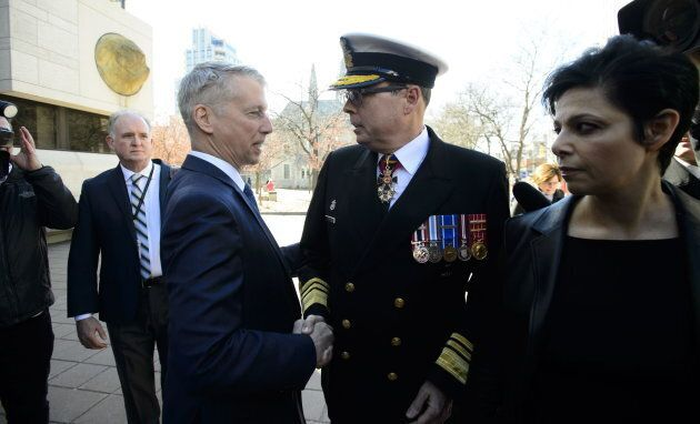 Liberal MP Andrew Leslie shakes hands with Vice Admiral Mark Norman as he arrives to court in Ottawa on May 8, 2019.