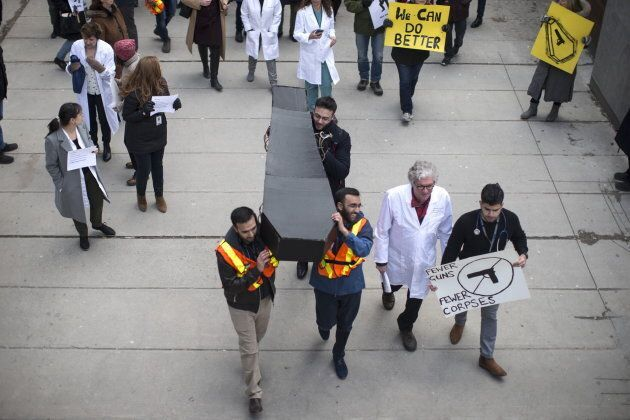 A model of a coffin is carried as physicians and health workers protest in Toronto on April, 3, 2019,...