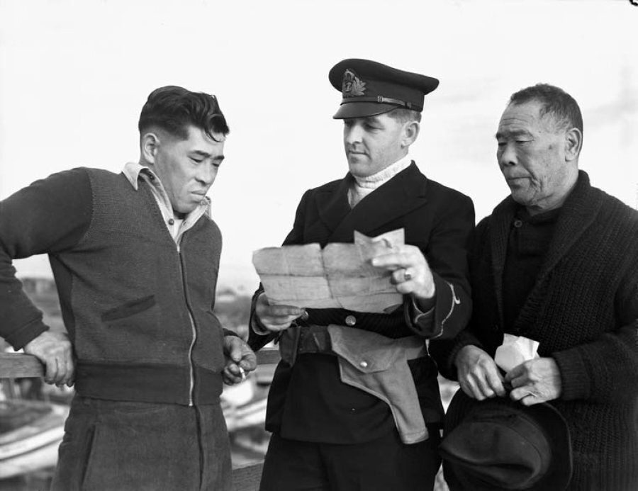Japanese-Canadian fishermen are questioned after having their boat confiscated by a Royal Canadian Navy...