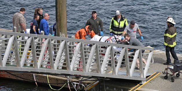 Emergency response crews transport an injured passenger to an ambulance at the George Inlet Lodge docks...