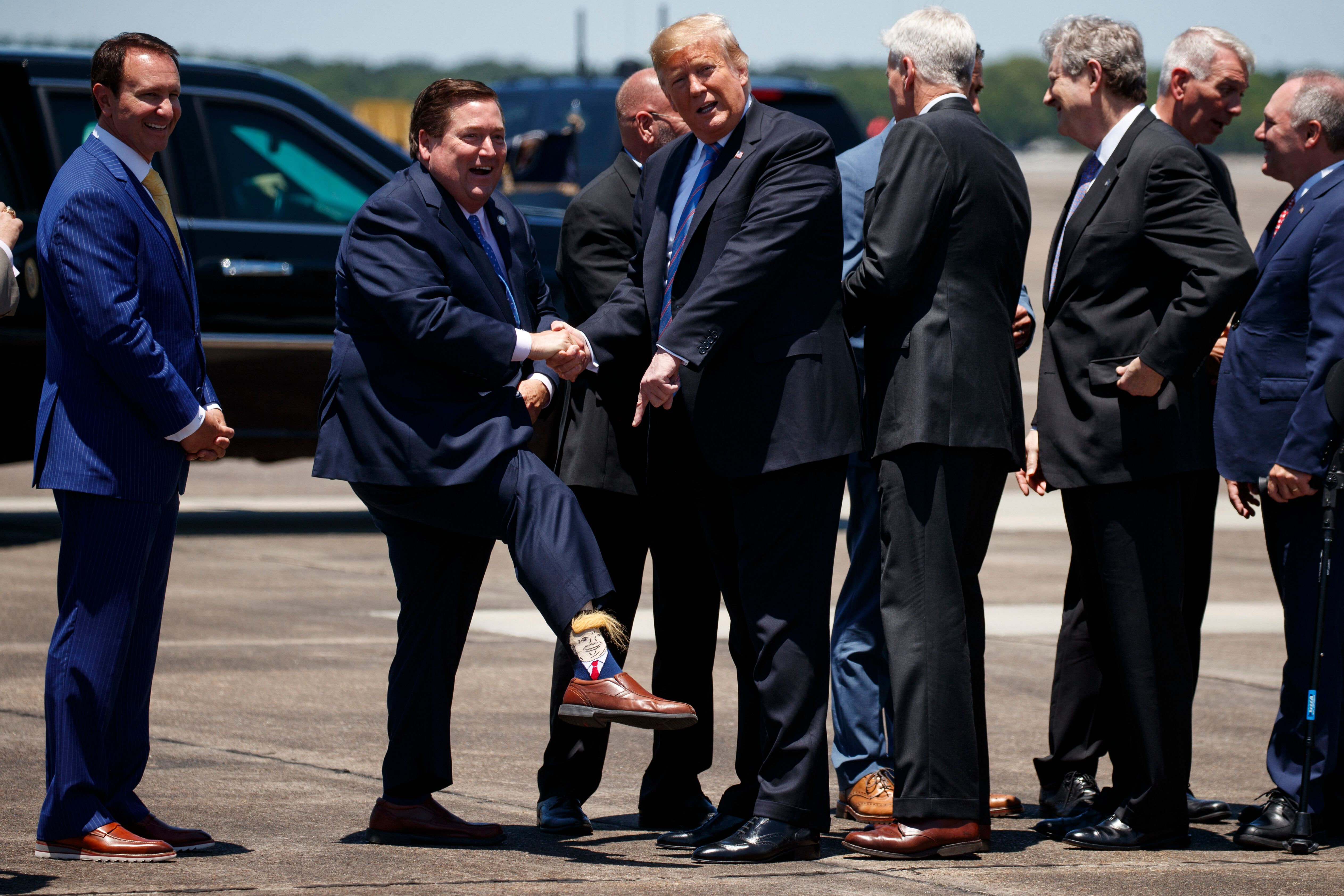 President Donald Trump looks the socks of Lt. Gov. Billy Nungesser, R-La., after arriving at Chennault International Airport, Tuesday, May 14, 2019, in Lake Charles, La. (AP Photo/Evan Vucci)