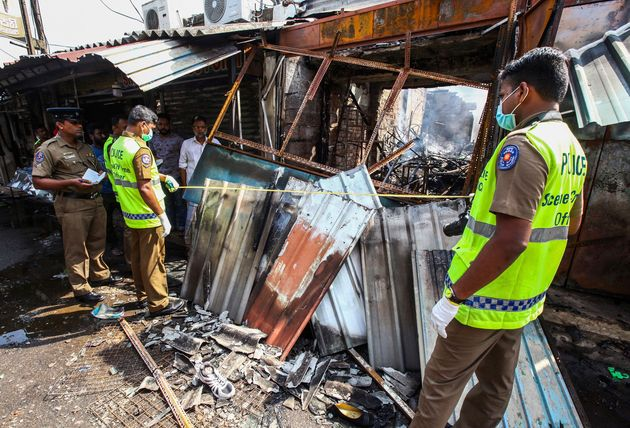 Sri Lankan security officers inspect vandalized shops owned by Muslims in Minuwangoda, a suburb of Colombo,...