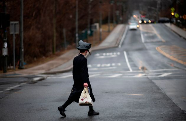 A youth crosses a street in Monsey, New York, where a measles outbreak has sickened scores of people,...