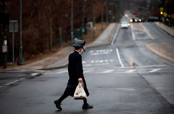 A youth crosses a street in Monsey, New York, where a measles outbreak has sickened scores of people, mainly from the Orthodo