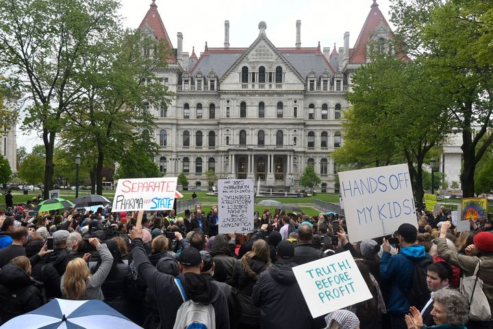 Protesters stand in the rain while protesting against legislation to narrow exemption to state-mandated vaccines at a rally a