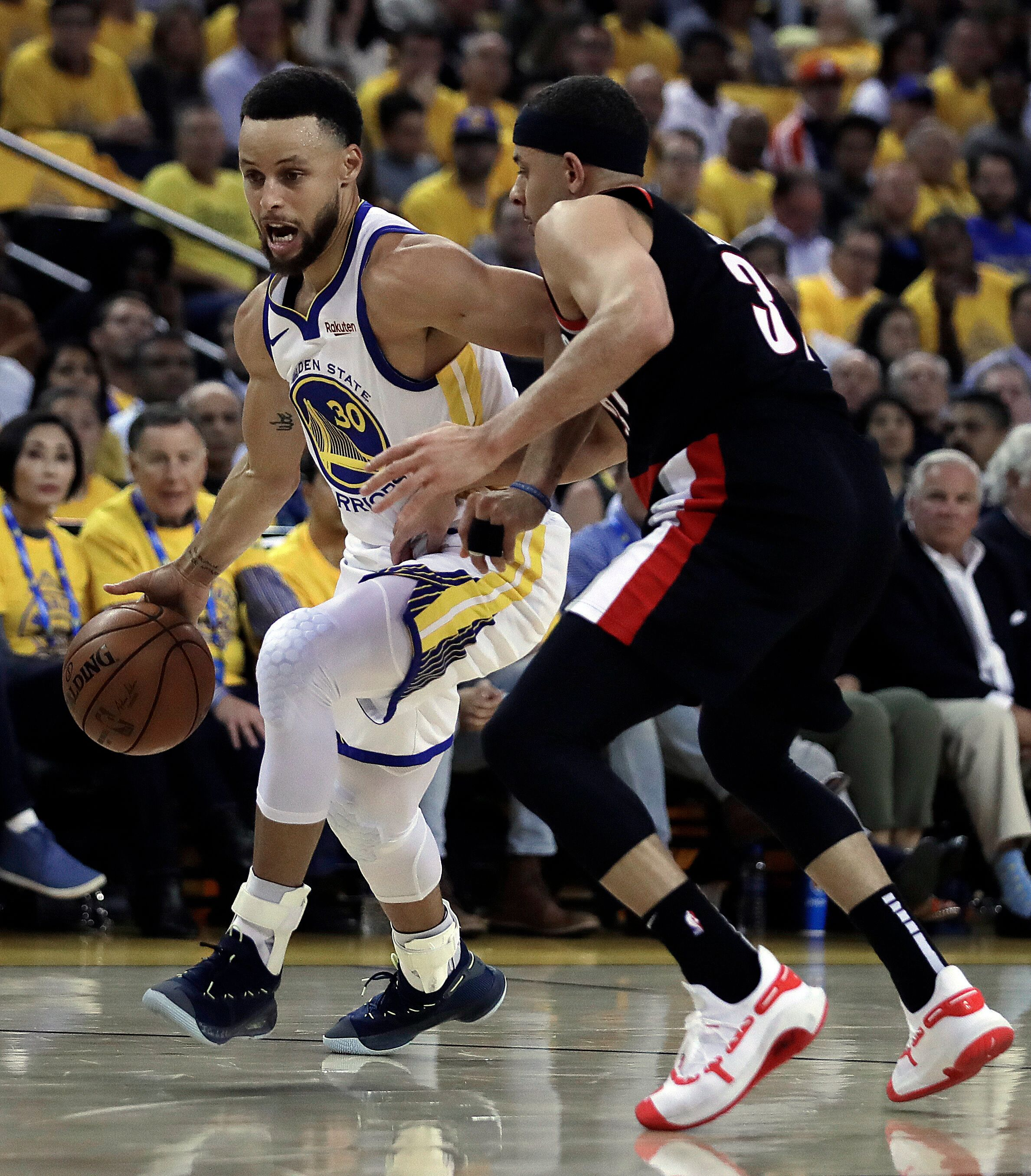 Golden State Warriors' Stephen Curry, left, drives the ball against his brother, Portland Trail Blazers' Seth Curry, during the first half of Game 1 of the NBA basketball playoffs Western Conference finals Tuesday, May 14, 2019, in Oakland, Calif. (AP Photo/Ben Margot)