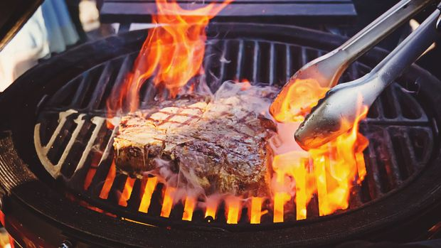 A piece of meat in flame. The cook flips a piece of meat beef on the grill with open fire. Steak on the grill with flames