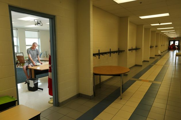 A teacher organizes his empty classroom in a Brampton, Ont. school in Aug. 31,