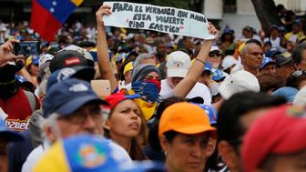 "An opponent of the Nicolas Maduro government holds up a homemade sign with a message that reads in Spanish: ""I demand punishment for the hangman who ordered this death"" during a rally led by opposition leader Juan Guaidó, in Caracas, Venezuela, Saturday, May 11, 2019. Guaidó has called for nationwide marches protesting the Maduro government, demanding new elections and the release of jailed opposition lawmakers.(AP Photo/Fernando Llano)"