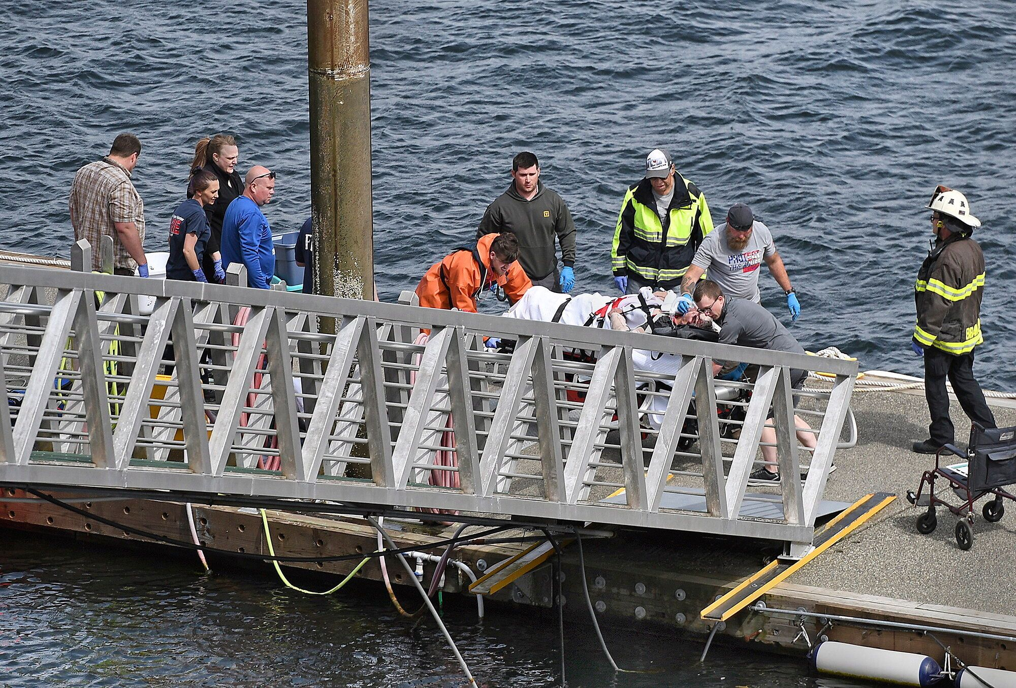 Emergency response crews move an injured passenger to an ambulance at the George Inlet Lodge docks, May...