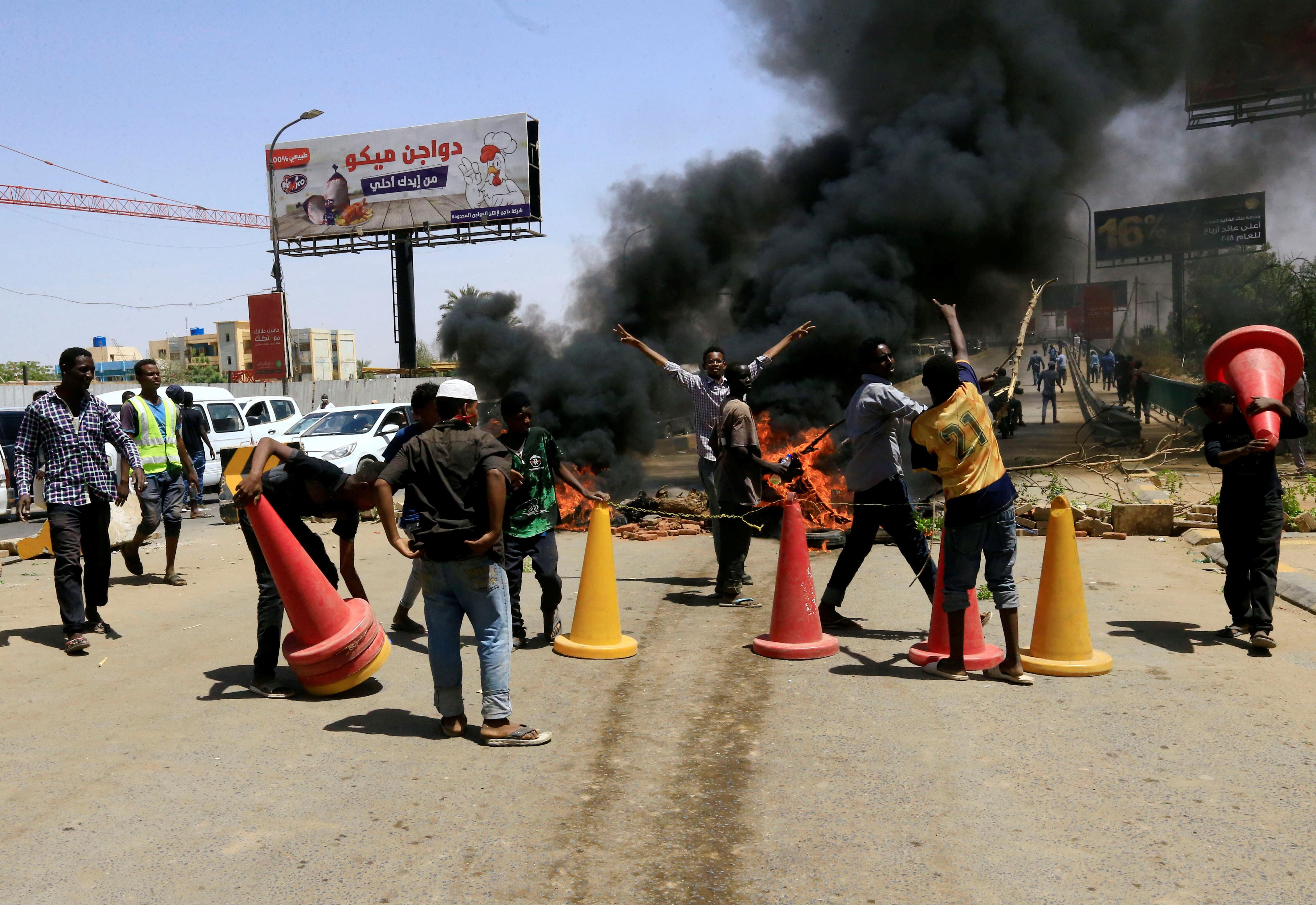 수단 시위대가 길을 막기 위해 쌓아놓은 타이어 등을 불태우고 있다. 수단, 하르툼. 2019년