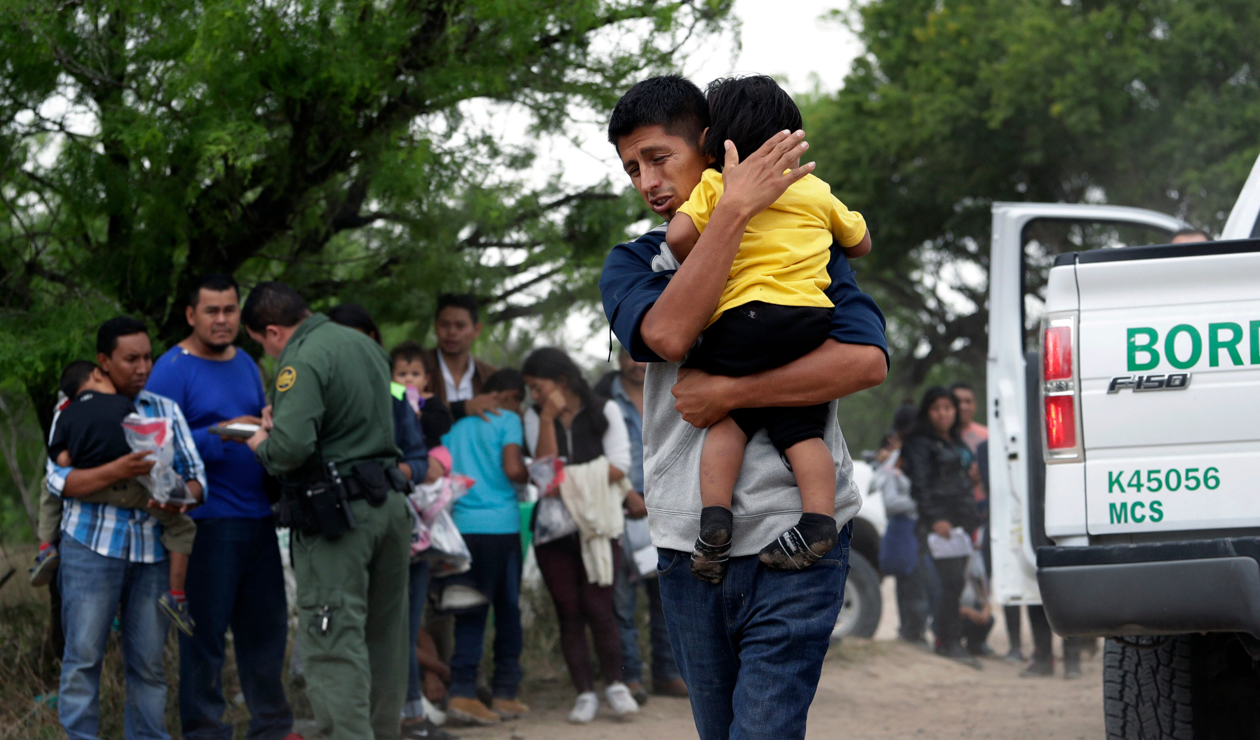 Migrant Jose Fermin Gonzalez Cruz holds his 2-year-old son, William Josue Gonzales Garcia, as they wait with other families w