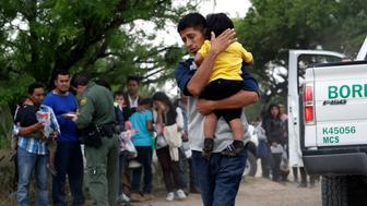 FILE - In this March 14, 2019, file photo, Jose Fermin Gonzalez Cruz holds his son, William Josue Gonzales Garcia, 2, as they wait with other families who crossed the nearby U.S.-Mexico border near McAllen, Texas, for Border Patrol agents to check names and documents. A surge in family arrivals, largely from Guatemala and Honduras, has led Border Patrol agents to shift attention from preparing criminal cases to caring for children. (AP Photo/Eric Gay, File)