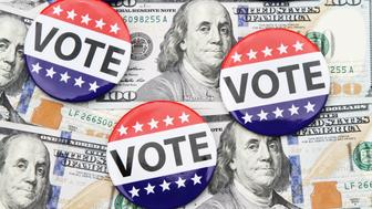 VOTE campaign buttons on top of scattered hundred dollar bills spread out beneath it. Concept image illustrating election funding, political donations, Super Pac money, political bribes.