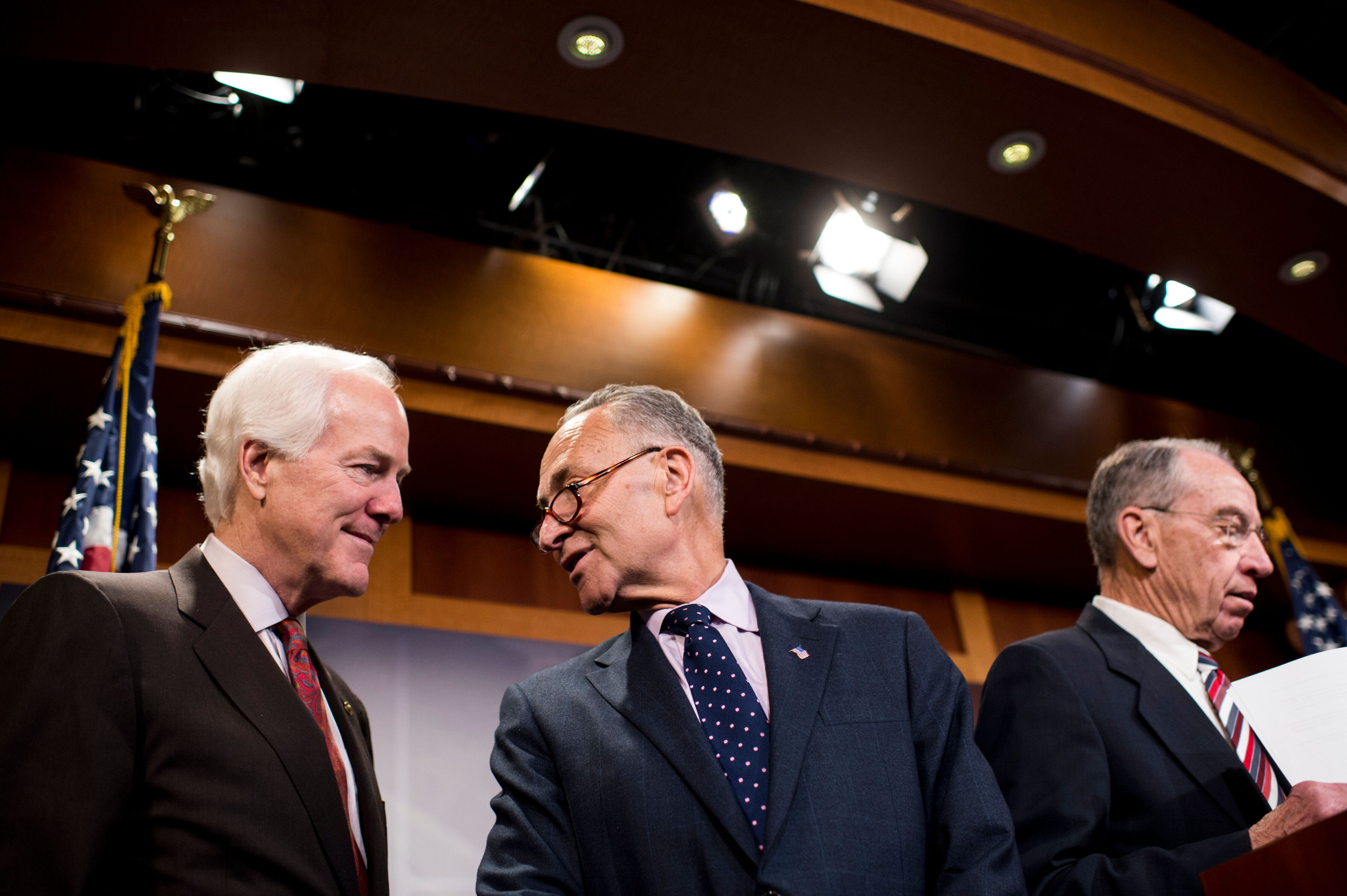 UNITED STATES - APRIL 29: Senators John Cornyn, R-Texas, left, and Chuck Schumer, D-N.Y., talk as chairman Chuck Grassley, R-Iowa speaks during the Senate Judiciary Committee members' news conference in the Capitol on bipartisan patent reform legislation on Wednesday, April 29, 2015. (Photo By Bill Clark/CQ Roll Call)
