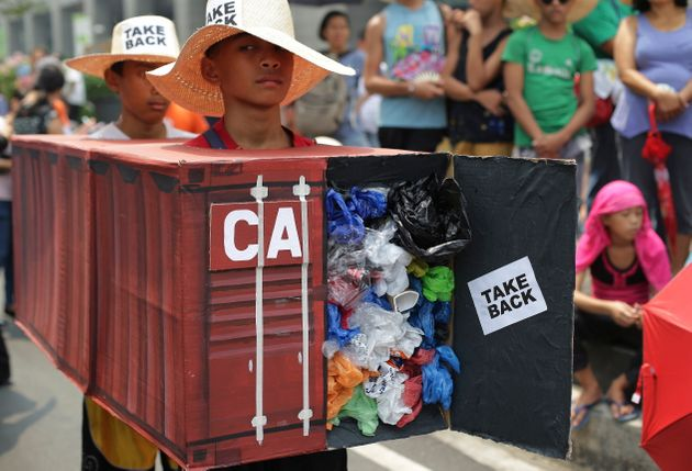 Filipino environmental activists wear mock container vans filled with garbage to symbolize the 50 containers...