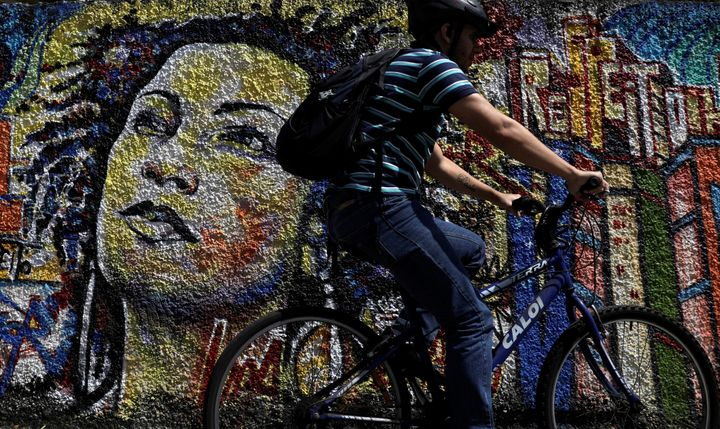A man rides past a graffiti in tribute of late councilwoman Marielle Franco, murdered in Rio de Janeiro in 2018.