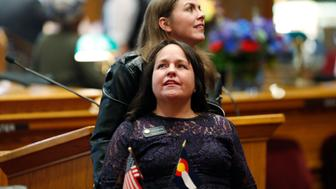 Colorado state Sens. Faith Winter, D-Thornton, foreground, and Kerry Donovan, D-Vail, look into the gallery as lawmakers convene for the new session in the Senate chamber in the State Capitol Friday, Jan. 4, 2019, in Denver. (AP Photo/David Zalubowski)