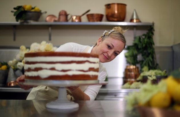 Claire Ptak puts the finishing touches on the wedding cake in the kitchens of Buckingham Palace in London,...